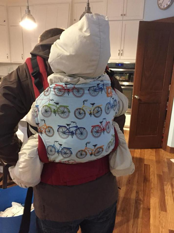 (Back of a brown haired white man in a brown jacket with a toddler in a puffy white snow suit on his back in a bicycle pattern Tula buckle carrier. They are standing in a kitchen.).