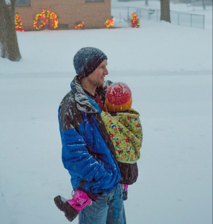 [Image of a white man smiling in the falling snow while wearing a child on his front. Both of them are wearing hats. The child has on pink and black winter boots. The child has a green blanket over the carrier tucked into the blue winter coat that the man has on. The neighbor across the street has on twinkling lights on the shrubbery.