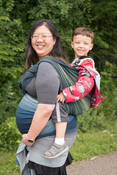 Image of a smiling east Asian woman with glasses in a grey and black dress. She has a blue and white gradient wrap around a pregnant belly. She also bas a green, yellow, and navy blue woven wrap on her back that is carrying a large, mixed-race preschooler in a red raincoat who is grinning hugely.