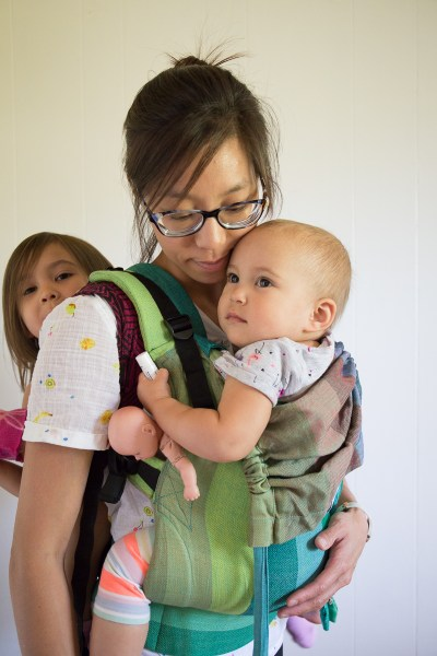 Image of a tan skin bespectacled Asian woman looking down at the toddler worn on her front in a green soft-structured buckle carrier. The toddler is looking in the distance and holding on to lip balm and a baby doll. On the woman's back is the toddler's older sibling who's wrapped in a woven wrap carrier.