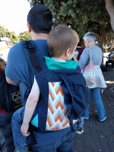 [Image of the back of a blonde white 4 year old boy in a Beco toddler on the back of a dark haired male caregiver.]