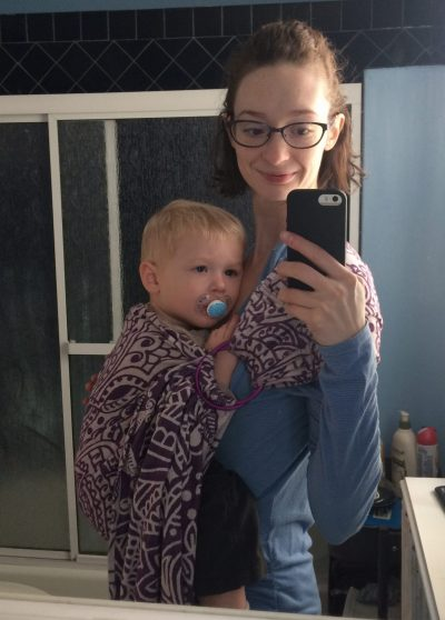 Image is a bathroom mirror selfie of a bespectacled white woman wearing a blonde white toddler in a purple ring sling on her front. The woman is smiling while the toddler is