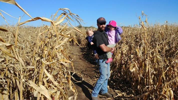 Image of a white bearded man in a black baseball cap wearing a white blonde infant boy on his back in a beco soleil while also holding a brunette toddler girl in his arms. They are in a corn maze.