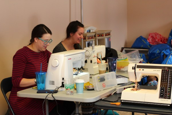 [Image of two white women with brown hair pulled back, sitting at a table with sewing machines and coffee and sewing notions. In the near distance are a pile of blue and red bags that are emptied of the carriers that usually contain.]