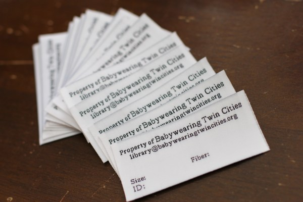 [Image of white fabric labels with black text. Header: Property of Babywearing Twin Cities. Subheader: library@babywearingtwincities.org. Text with space for writing in: Size, ID, Fiber. The pile of labels lay on a wood surface.]
