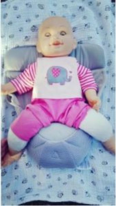 image of a demonstration doll seated in an infant insert that goes in a soft-structured carrier