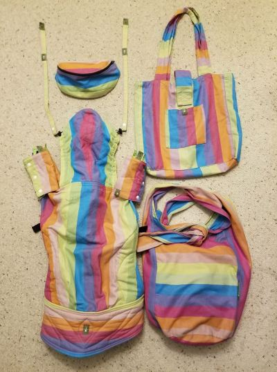 Image of several Lenny Lamb babywearing items on a sand colored back ground. All the items are in the same Lenny Lamb wrap material in the Coral Reef pattern which involves thick stripes of orange, lemon, cream, turquoise, magenta, and blue violet. On the left is a toddler carrier, including matching suck pads on the straps and reach straps leading off the hood. Above that is a waist sack (fanny pack). On the right top is a shopping bag laid flat with a pocket in the front that is big enough to hold a folded carrier, and on the right bottom is a hobo bag with thick straps tied into a knot that is big enough to hold 3 carriers. Or 1 carrier and diapers, wipes, wallet and snacks.
