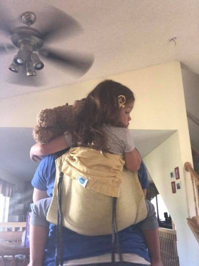 Image from the back of a toddler in a yellow linen onbuhimo carrier with the hood partially cinched with the dangling black chambray reach straps along both sides of the hood.