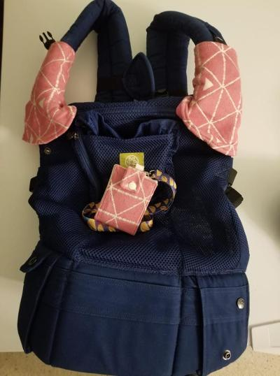 Image of a navy blue Lillébaby Airflow on a white background. The carrier has suck pads made out of Tekhni candy delta wrap scrap. The material is a bold candy pink with white geometric lines that intersect to form triangles. Laying in the middle of the carrier is an ID/card wallet made out of matching Candy Delta material.