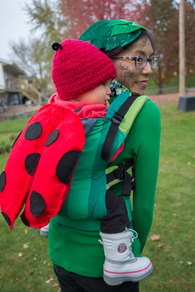A Mama is dressed up as a plant with a felt leaf fascinator, green vines drawn on a greenish face, green shirt. She's wearing a toddler on her back who has on a red crocheted hat with black pipe cleaner antennae and red felt ladybug wings with black felt dots. the ladybug is worn in a green striped carrier on Mama's back. They're outside on a cloudy autumnal day.