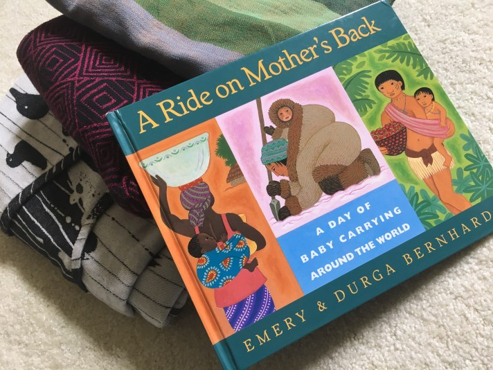 "A book rests on three neatly folded woven wrap baby carriers. Book is titled ""A Ride on Mother's Back: A Day of Baby Carrying Around the World"" by Emery & Durga Bernhard."" It features illustrations of three caregivers wearing babies in different ways."