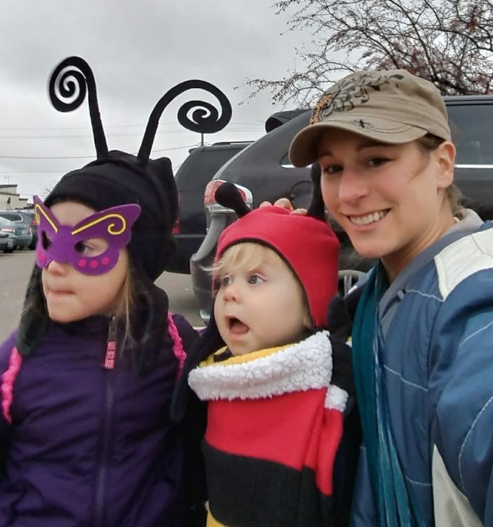 Image of a white woman in hat and winter coat wearing her blonde son forward facing with a red, yellow, white and black striped carrier cover over him. He is wearing a red and black winter hat with antennae (representing a caterpillar). Next to them is a young white girl in a black and and purple butterfly costume. The mom is smiling at the camera, the 2 children are both looking out of frame in surprise.