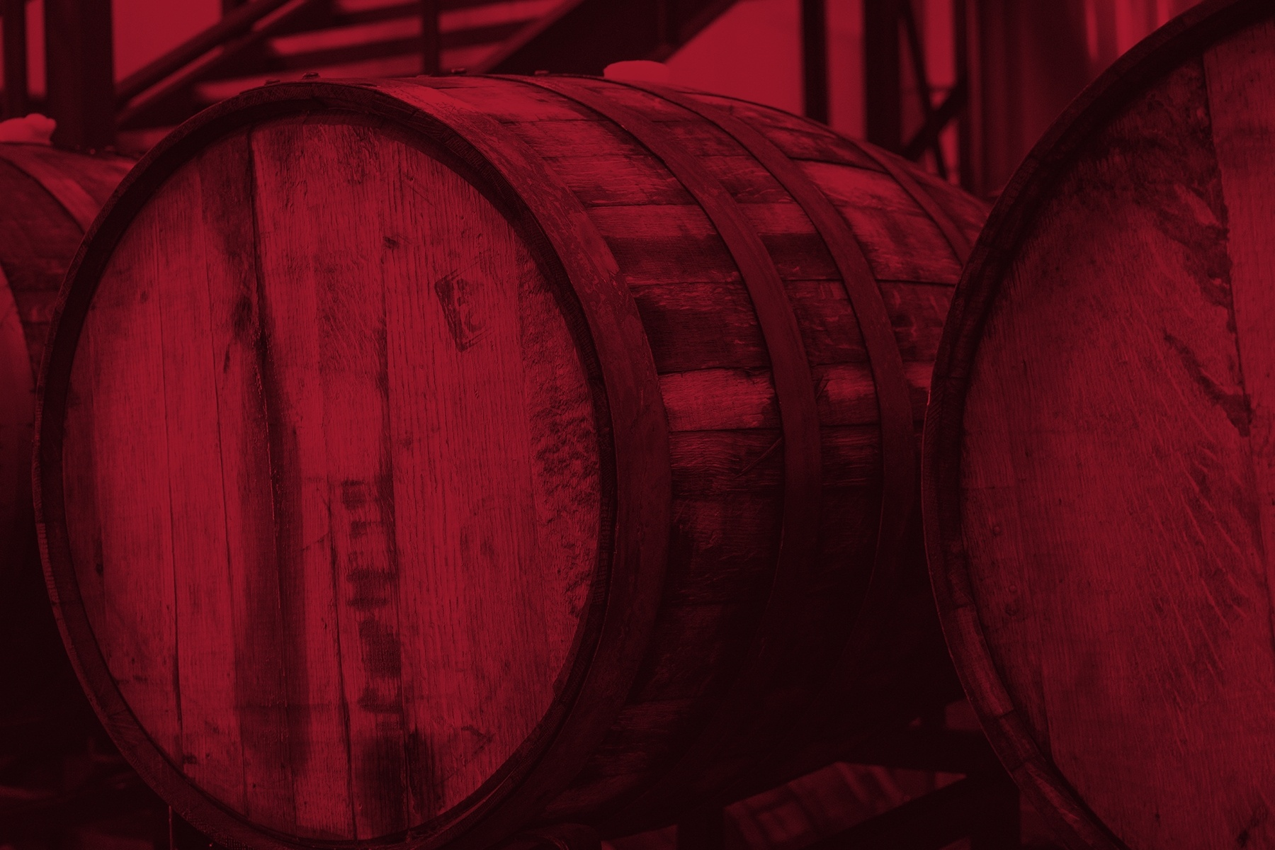 large wooden barrels used to store alcohol with red image overlay