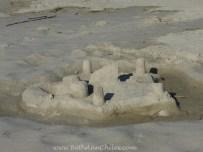 Cute sand castle on the beach across from the lighthouse