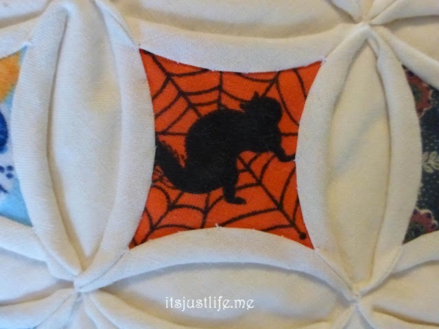 A Halloween tablecloth featured black cats and spider webs.