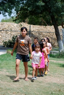 Marilin leads the younger children at the children's home to a group Bible lesson