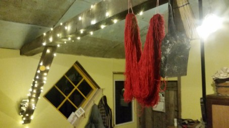 The skein drying over my wood stove basking in the faerie lighting