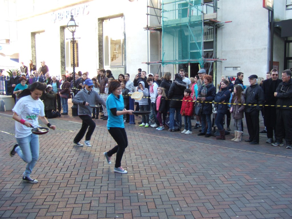 Exercise this image shows Claire from Lushington Chiropractic Clinic running pancake race in Eastbourne to raise funds for St Wilfrid's Hospice.