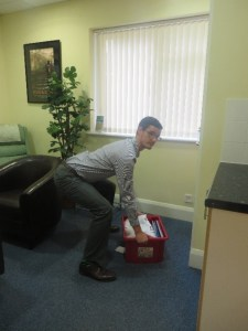 Mykel Mason, doctor of chiropractic, shown bending the knees and curving the low back forwards which will increase disc pressure, in picture 1; and shown lifting a box bending his knees and hips keeping the low back straight to reduce disc pressure in picture 2.