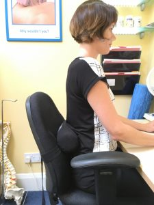 Image shows Eastbourne Doctor of Chiropractic Victoria White sitting at the desk with a lumbar roll attached to the back of the chair.