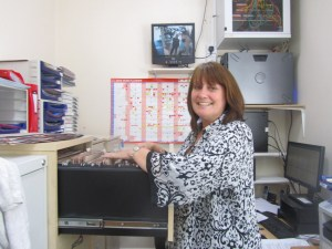 Blog on clinic assistants Images shows clinic assistant Judy standing at the filing cabinet, pulling guest files for the next day