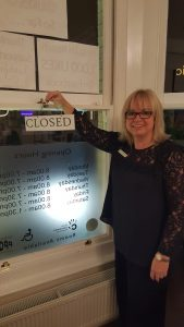 Blog on clinic assistants. Image shows Theresa about to turn the sign from open to closed.