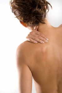 Image shows women rubbing the left hand side of her neck.