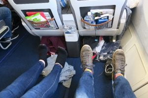 Image shows couple doing in-flight exercises by rotating their ankles in each direction