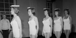 Image shows ladies balancing a book on their head to insure a good posture stance.