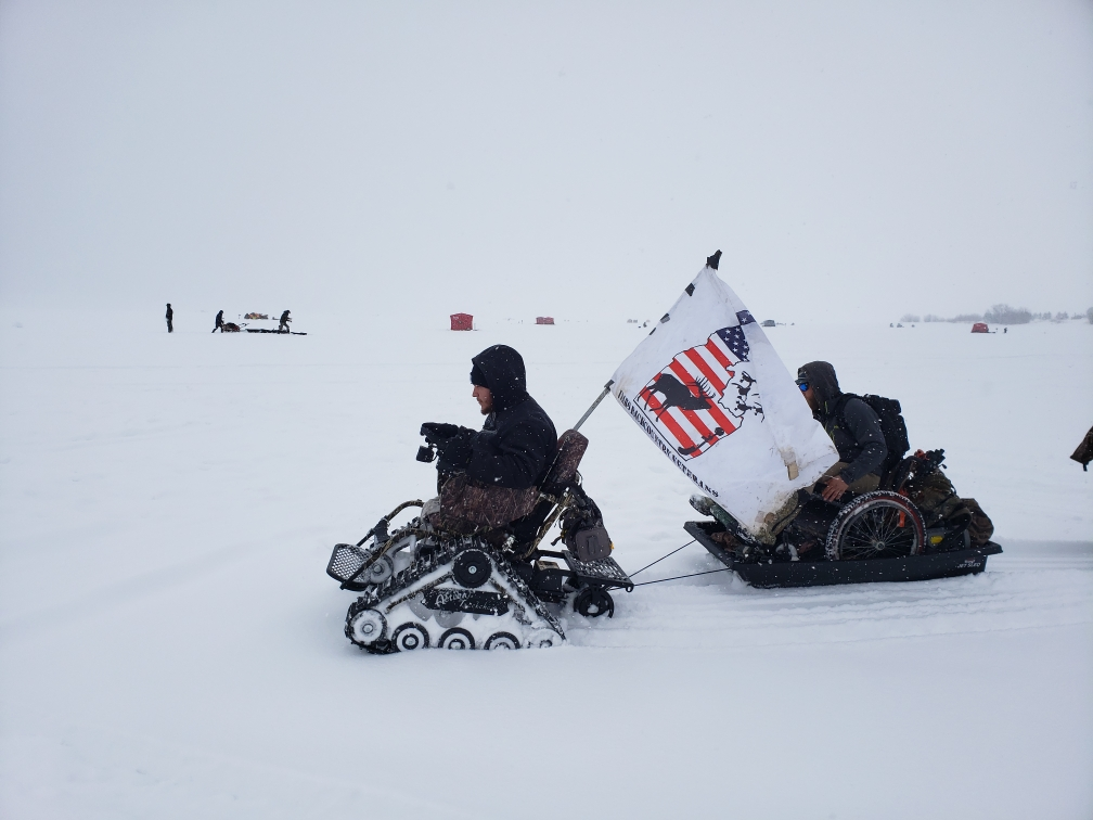 Veteran in a tracked wheelchair pulling sled with Veteran in traditional wheelchair