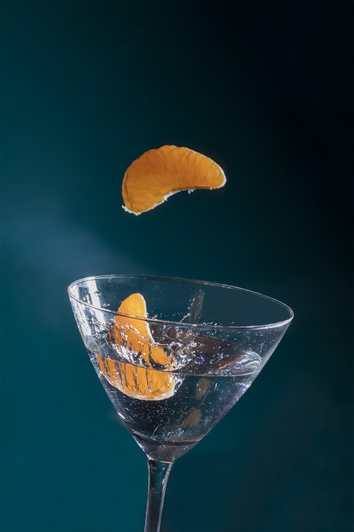 otro angulo de mandarina cayendo a copa de coctel
