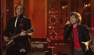 Image: Arcade Fire frontman wearing red square performs with Mick Jagger
