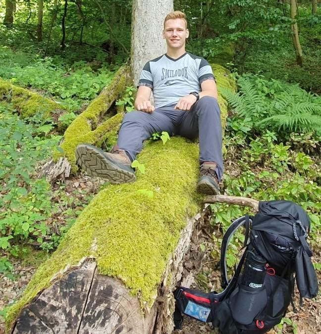 Ein Bild von Mir beim Wandern in Bad Lauterberg auf einem mit Moos bewachsenen Baumstamm.