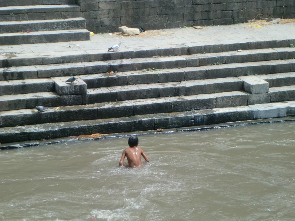 対岸で遺体が燃やされている川で水浴びする子供
