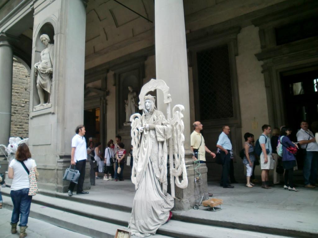 大道芸人がウッフィツィ美術館の前に並ぶ大勢の人を楽しませる。