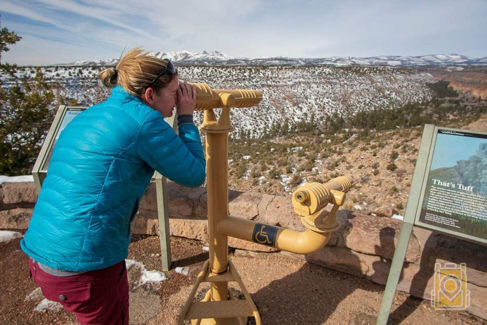 How to Spend a Day in Bandelier: Tiffany gazes through a scope into Frijoles Canyon in Bandelier National Monument