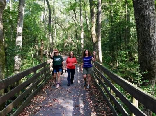 three women walking a boardwalk