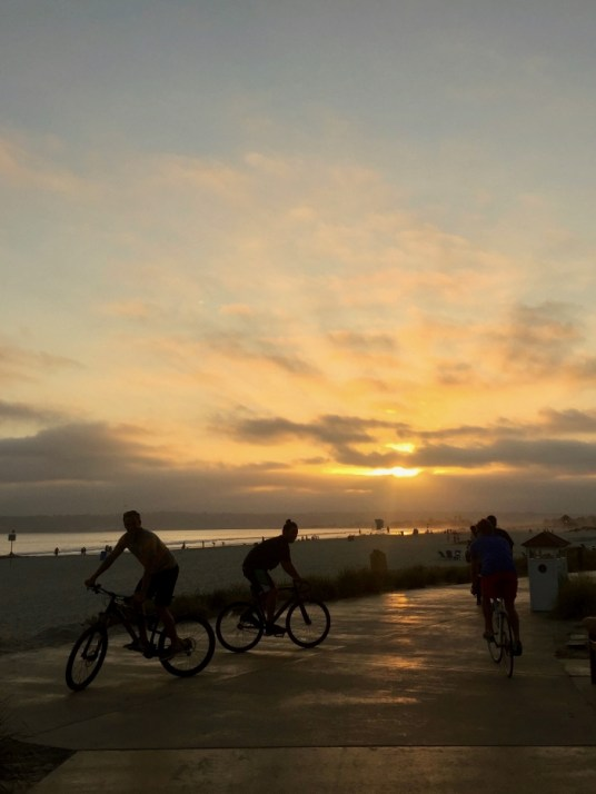 People riding bicycles at sunset