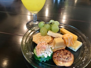 plate of cheese, crackers, grapes, and finger food