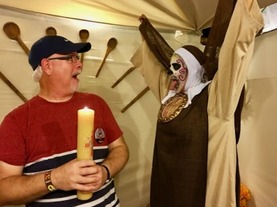 screaming man holding candle with scary nun