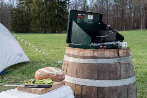 A camp stove set up on a barrel next to a loaf of bread and some veggies.