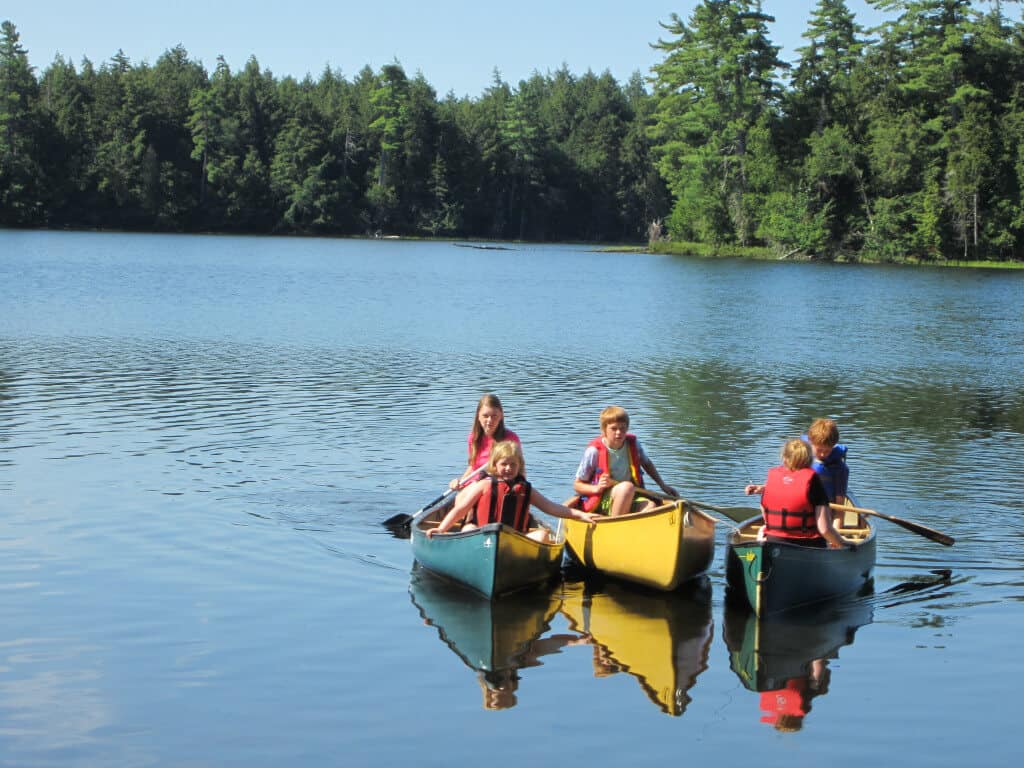 Three canoes side-by-side on a mountain lake in the St. Regis Canoe Area. There are five kids paddling.