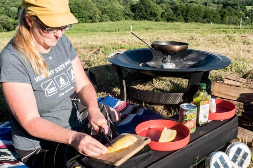 A woman prepares a camp meal next to a campfire.