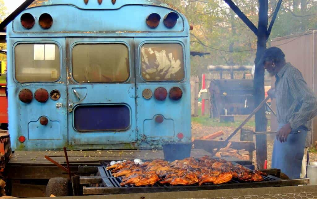 Curtis of Curtis BBQ, cooking meat on a grill behind a blue school bus.