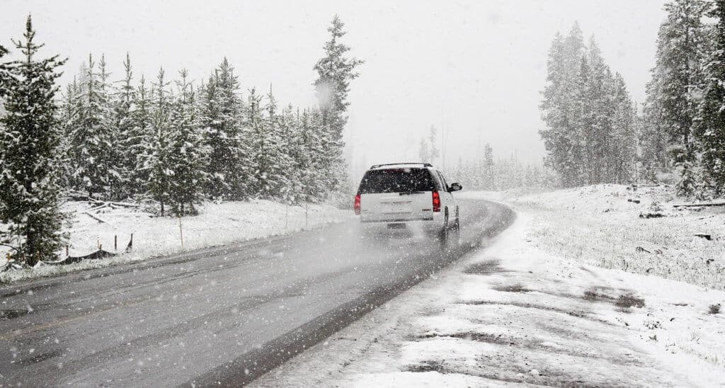 A white SUV drives along a snowy road on a winter road trip