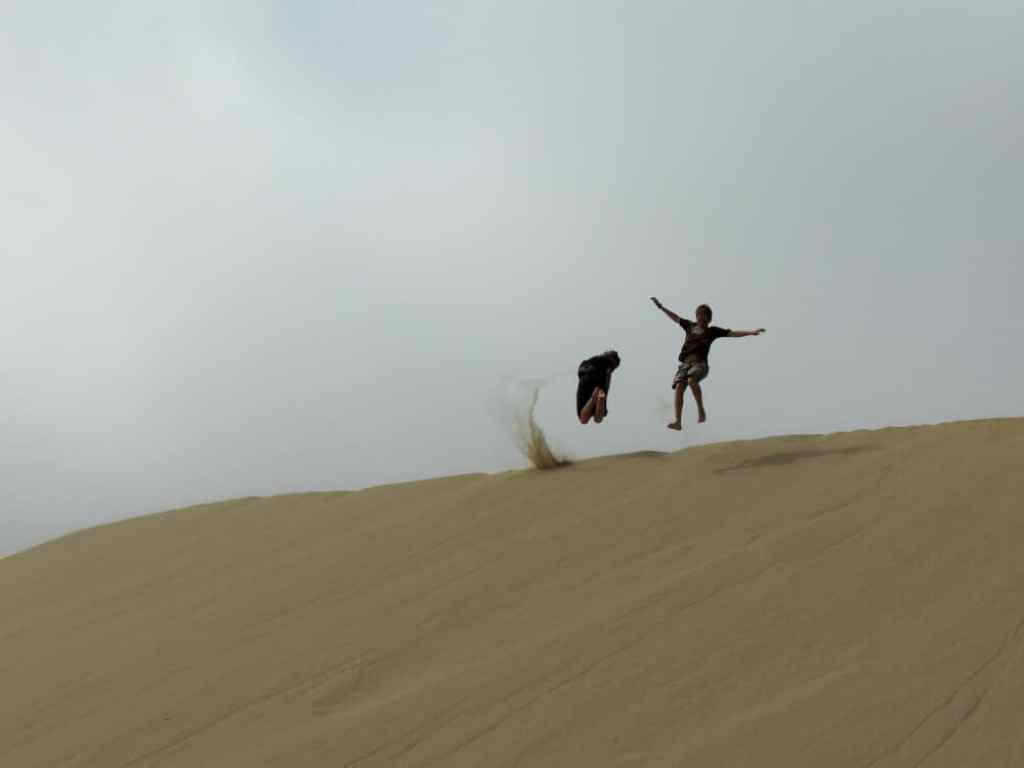 Two kids jumping in the sand at Oregon Sand Dunes