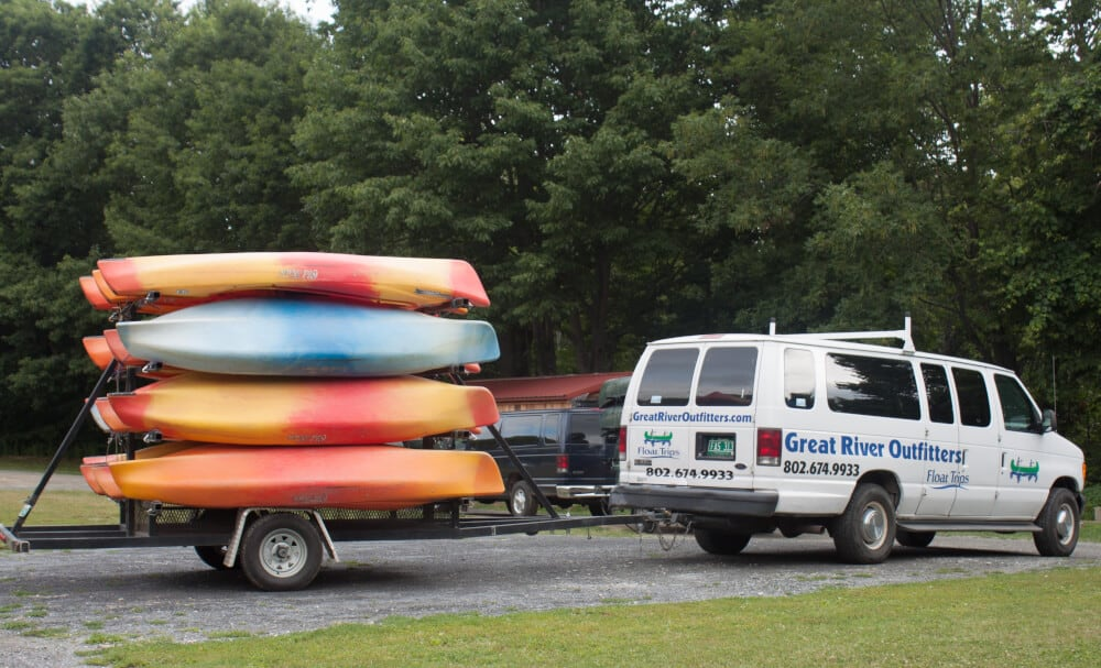 A white van pulls a trailer full of colorful kayaks. Great River Outfitters.
