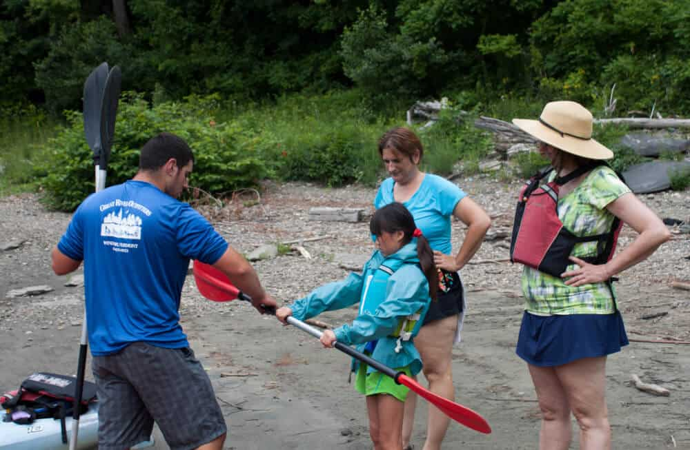 Two women and a girl learn how to hold a kayak paddle on a beach