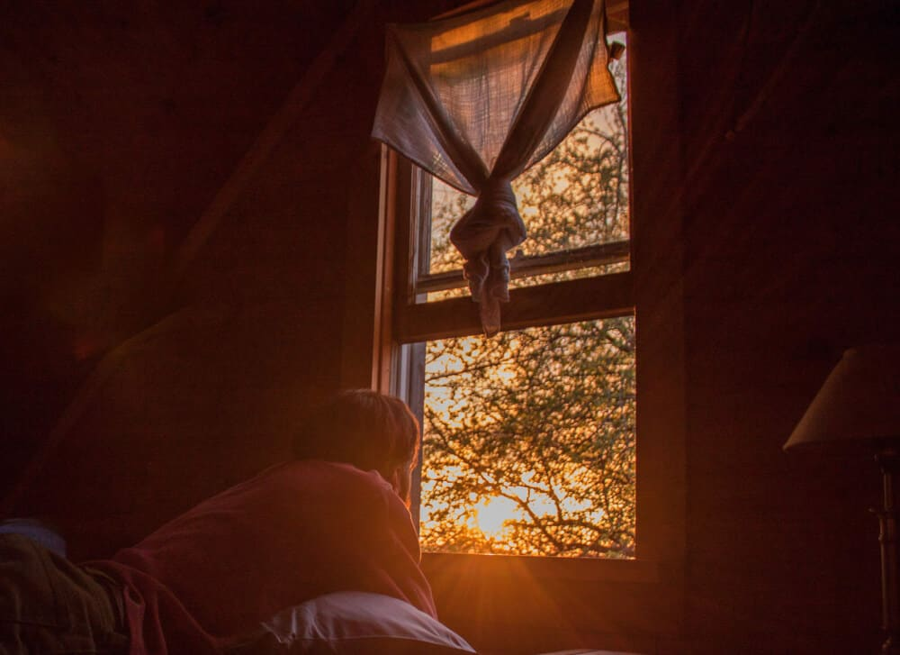 Eric looking out the window at the sunset from the dark sleeping loft.