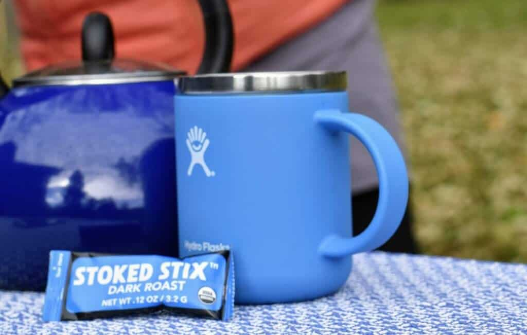 A blue camping coffee mug, a blue tea kettle, and an instant coffee packet called Stoked Stix